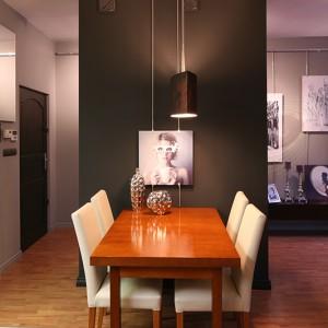 Przy ścianie kominowej, wyróżnionej kolorem czarnym, zaaranżowano kącik jadalniany. Wykonany z aluminium system zawieszania obrazów powstał na zamówienie, według projektu architektów. Fot. Bartosz Jarosz.
