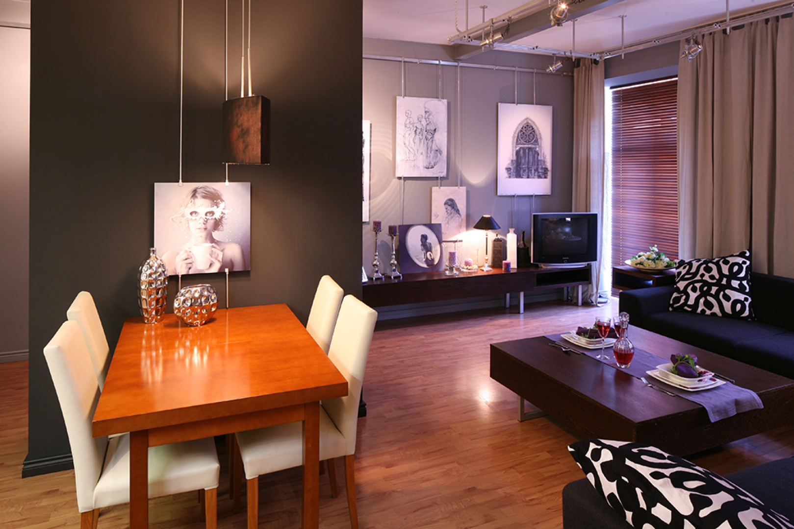 Fotografia autorstwa Kassandry umieszczona nad stołem bezwiednie przyciąga wzrok. Ceramiczne dzbany utrzymane w tonacjach srebra stanowią wyraźny element dekoracyjny. Kolorystyką nawiązują do elementów systemu podwieszeń wykorzystanych w apartamencie. Fot. Bartosz Jarosz.