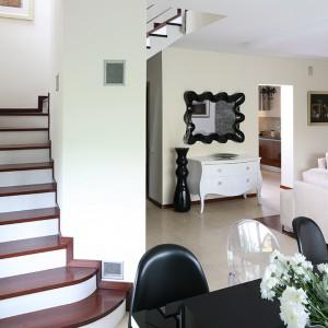 Kuchnia sąsiaduje bezpośrednio z salonem; stanowi oddzielne, jednak nie zamknięte drzwiami pomieszczenie. Jednolity materiał podłogowy w kuchni i w części salonu optycznie łączy strefy oraz akcentuje spójność stylu wszystkich wnętrz. Fot. Bartosz Jarosz.