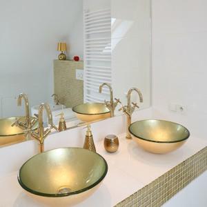 W łazience dla pani i pana domu – dwie umywalki oraz dwie baterie; cały zestaw w złotym kolorze. Dekoracyjne wykończenie równoważy prosta forma mis oraz armatury. Fot. Bartosz Jarosz.