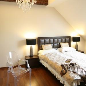 Sypialnia z elementami glamour, jak tapicerowany zagłówek łóżka czy biżuteryjne lampy. Klimat rustykalny wprowadzają beli sufitowe, które także wizualnie zwiększają przestrzeń. Fot. Bartosz Jarosz.