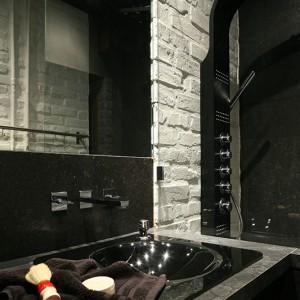 Szklana umywalka w kolorze czarnym została osadzona w blacie; dobrano do niej ścienną baterię podtynkową z dwoma uchwytami. Fot. Bartosz Jarosz.