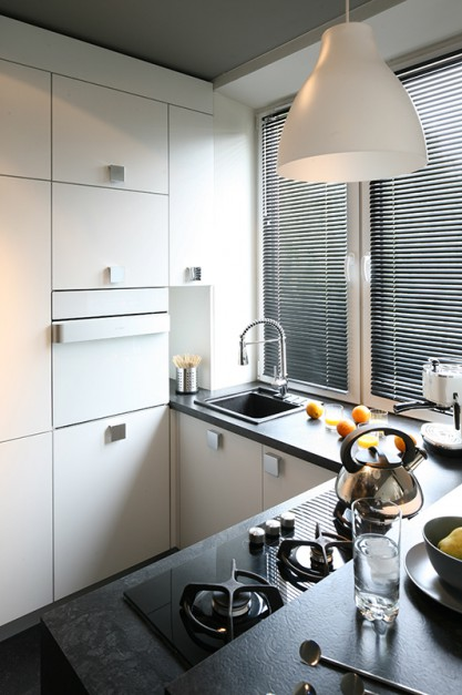 Dla kontrastu, do białych frontów dobrano ciemne, grafitowe blaty oraz wyposażenie: płytę grzejną (IKEA) oraz zlewozmywak kompozytowy (Alveus). Fot. Bartosz Jarosz.