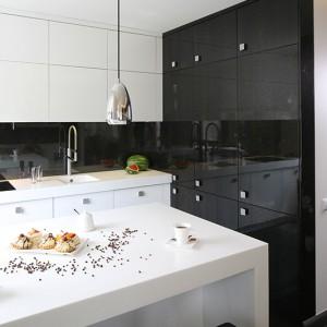 Biel i czerń zabudowy kuchennej (EBANO Design) subtelnie ze sobą współgrają, ciesząc oko swym blaskiem. By nie zaburzyć tej wizualnej harmonii, sprzęt AGD dyskretnie ukryto za efektownymi frontami. Fot. Bartosz Jarosz.