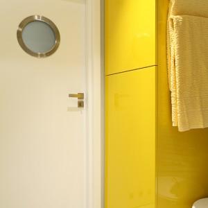 Ten kolor budzi do życia. Projektantka wybrała lekko musztardowy odcień lakieru do wykończenia płyt MDF. Tak powstała szafa, która mieści pralkę oraz półki. Bulaj w drzwiach (Pol-Skone) akcentuje nadmorski klimat aranżacji. Fot. Bartosz Jarosz.