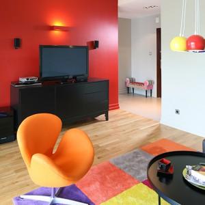 Czerwień pojawia się zarówno na ścianie w salonie, w jadalni, jak i przy wejściu do kuchni. Fot. Bartosz Jarosz.