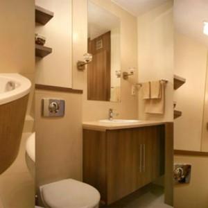 """27-doris. """"Elegancka, romantyczna łazienka urządzona w brązach i beżach, która zapewnia komfort i relaks po ciężkim dniu pracy. Materiały użyte to: blat marmurowy Crema Marfil oraz płytki 60x60cm w tym samym odcieniu,meble robione na zamówienie - fornir Rigoletto Tabac. Wanna obłożona jest płytą hdf w tym samym wykończeniu co meble""""."""