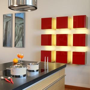 Na granicy kuchni i salonu dekoracyjny zestaw wiszących szafek z frontami z czerwonego, lakierowanego MDF-u w kształcie kwadratów. Wykorzystywane do przechowywania szkła nadają także kuchni salonowy charakter. Fot. Monika Filipiuk-Obałek.
