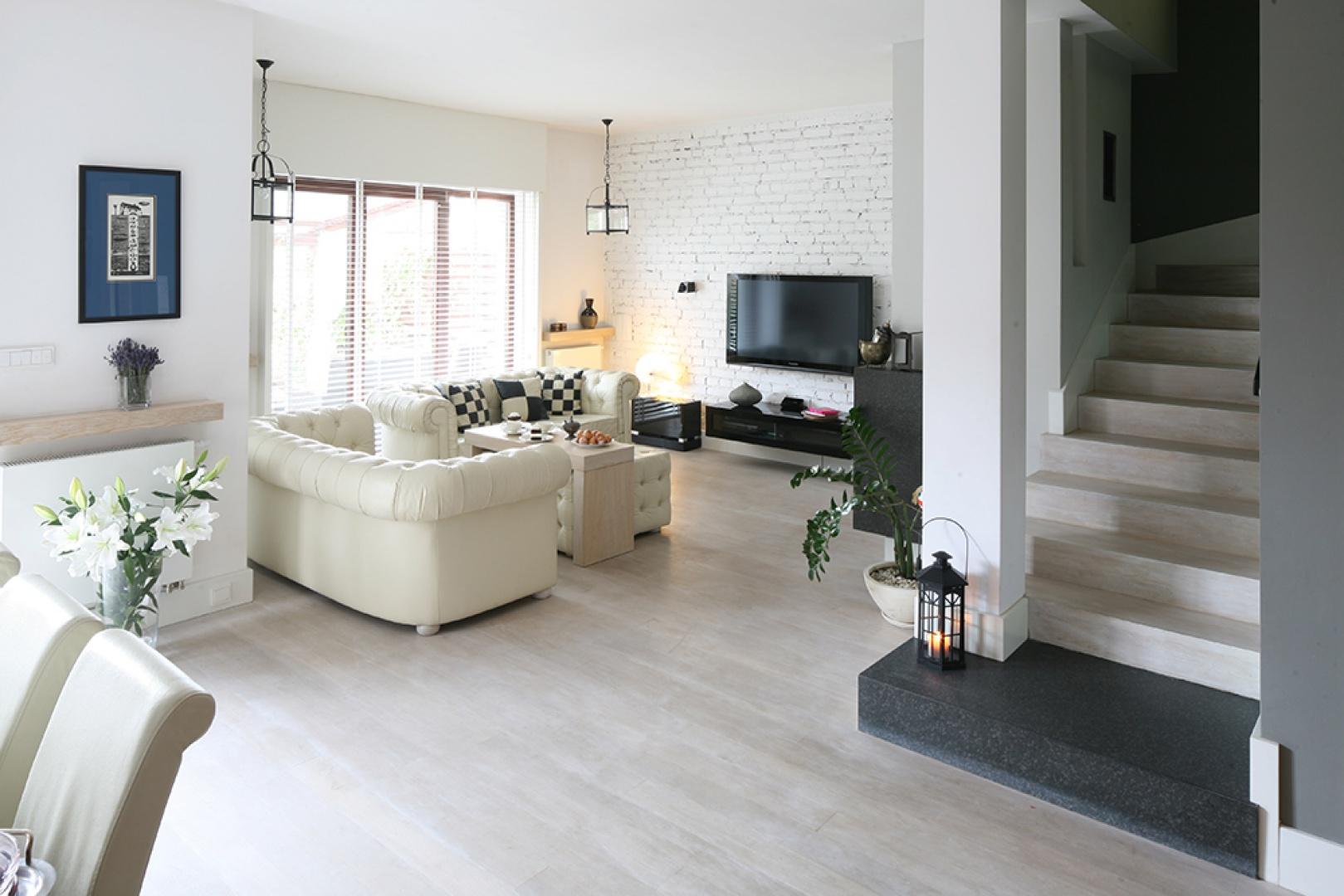 Miękkie, pikowane kanapy ocieplają surowe, nieotynkowane ściany. Nieco chłodne wnętrze stało się dzięki temu idealnym miejscem wypoczynku. Fot. Bartosz Jarosz.