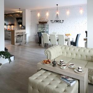 Salon płynnie łączy się z jadalnią i kuchnią, tworząc wspólną przestrzeń, bez granic i podziałów. Całość utrzymana jest w spójnych barwach bieli i szarości. Fot. Bartosz Jarosz.