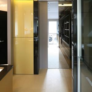 """Bezpośrednio z łazienki można przejść do garderoby, a następnie pralni.  Taki układ pomieszczeń  jest wygodny i funkcjonalny: czyste rzeczy trafiają na  półki tuż obok. Strefy oddzielają przesuwne drzwi  z brązowego szkła. Na podłodze płytki Atlas Concorde  z serii """"Glow Sun"""". Fot. Bartosz Jarosz."""