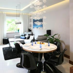 Jadalnię wydzielono w strefie salonu. Godne miejsce dla siebie znalazły tu klasyki designu Vernera Pantona w komplecie z okrągłym stołem i efektownym żyrandolem. Fot. Bartosz Jarosz.