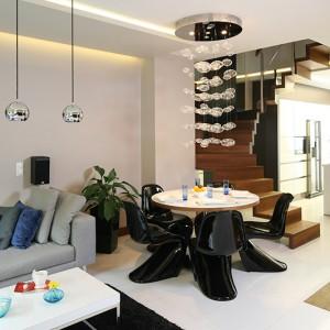 """Jadalnia znajduje się w strefie salonu. Tworzą ją stół z hartowanego, lakierowanego szkła i drewna (thermo jesion) oraz czarne krzesła Vitra """"Panton"""". Fot. Bartosz Jarosz."""