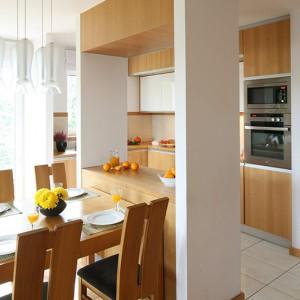 Kuchnia, mimo iż jest otwarta, nie pozostaje całkowicie na widoku. Od jadalni i salonu oddziela ją kredens z nadwieszoną szafką pomiędzy dwiema ściankami działowymi. Fot. Bartosz Jarosz.