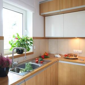 Ściany nad blatem kuchennym zabezpieczają płytki gresowe w jasnobeżowym kolorze (takim samym jak na podłodze). Zlewozmywak z ociekaczem, usytuowany dokładnie pod oknem, to produkt firmy Teka. Fot. Bartosz Jarosz.