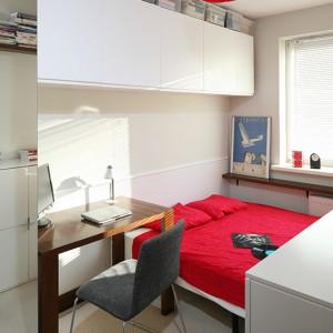 Utrzymaną w minimalistycznej bieli sypialnię ożywiają dodatki w kolorze intensywnej czerwieni. Drugie biurko, będące alternatywą dla stołu w jadalni, pozwoliło uniknąć bałaganu w salonie. Fot. Bartosz Jarosz.
