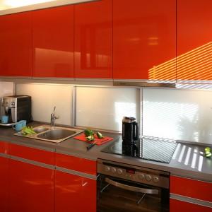 Materiały wykończeniowe we wszystkich pomieszczeniach miały z zasady być w jednolitej kolorystyce i o jednorodnej strukturze. Wyjątek stanowi  utrzymana w barwie czerwonej pomarańczy zabudowa kuchenna. Fot. Bartosz Jarosz.