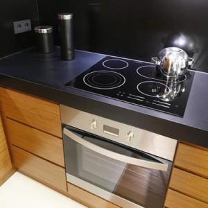 W tej kuchni fronty szafek kuchennych zostały wykonane z forniru modyfikowanegodrewna teakowego. Blat roboczy oraz środkowy pas – z czarnego MDF-u w wykończeniupółmatowym. Proj. Katarzyna i Michał Dudko, Formativ.