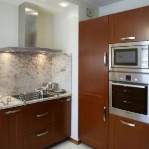 """Elegancki granit """"Shivakashi"""" nie tylko tworzy kuchennyblat, ale też pokrywa ściany nad nim do stosunkowo dużej wysokości. Dzięki temu niegroźne im żadne kulinarne szaleństwa. Proj. Barbara Gryt."""