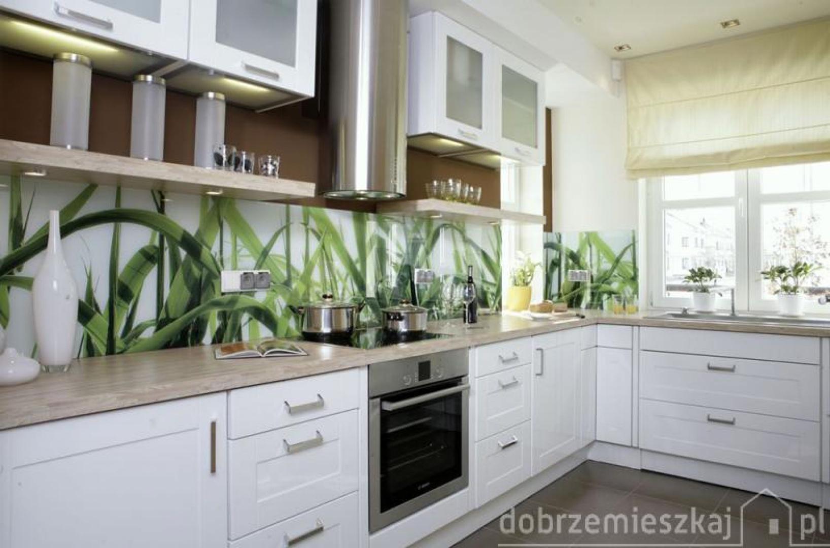 Ścianę nad kuchennym blatem pokrywa szkło podklejone folią, na której wydrukowano zdjęcia roślin. Ta w sumie prosta technika pozwala ozdobić każdą powierzchnię, nawet tak narażoną na zabrudzenia, jak ściana nad zlewem, naszym ulubionym motywem malarskim czy fotografią. Trzeba tylko zaopatrzyć się w szkło o odpowiedniej odporności i fachowców, którzy zadbają o szczelność wykonania. Proj. Lucyna Stefaniak.