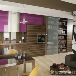 Fiolet frontów wiszących szafek kuchennych (lakierowany mdf) kontrastuje z wzorem drewna zebrano, który pojawia się w dalszej części zabudowy i brązem pokrytej szkłem ściany nad blatem. Proj. Paweł Ejsmont.