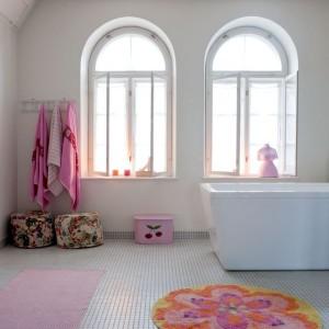 Obszerna łazienka z klasyczną mozaiką z lat 30. jest jasna i pełna światła. Prosta wolno stojąca wanna zapewnia maksimum komfortu. Nienaganną biel ocieplają  kolorowe wesołe dodatki. Fot. Sian Williams/Narratives.