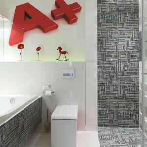 """Ta łazienka na piętrze jest nieco bardziej """"szalona"""" niż reszta pomieszczeń. W otoczeniu płytek o jednolitym kolorze, te z graficznym nadrukiem wyróżniają się szczególnie. Do tego czerwone, ogromne literki i nietuzinkowy wygląd gwarantowany. Fot. Bartosz Jarosz."""