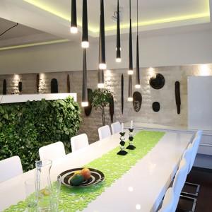 Przestrzeń jadalni wypełnił ogromny biały stół z lakierowanego MDF-u oraz piękne, wiszące lampy. Ozdobne oświetlenie widoczne jest zresztą w całym domu. Fot. Bartosz Jarosz.