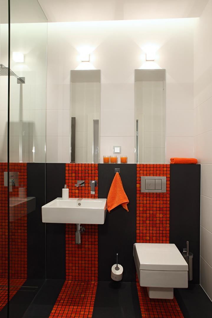 Trzy pasy pomarańczowej mozaiki biegną wzdłuż osi sanitariatów i prysznica. Dzięki zastosowaniu czarnej fugi jej kostki zdają się być nałożone na czarne, gresowe płytki. Fot. Monika Filipiuk-Obałek.