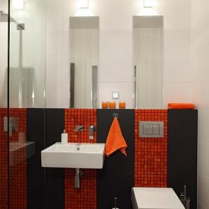 """Trzy pasy pomarańczowej mozaiki z serii """"Cube"""" Ardea Arte, umieszczonej na tle czarnych płytek gresowych Agrob-Buchtal biegną dokładnie w osi sanitariatów i prysznica. Ich kontynuację stanowią lustra oświetlone halogenami (z oferty BPM-Lighting). Proj. Monika Filipiuk-Obałek."""
