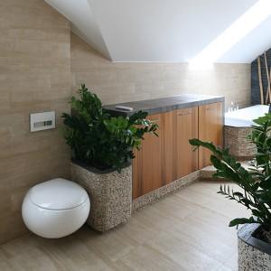 """Atutem pomieszczenia jest  lokalizacja pod skosem dachowym; okna zapewniają  światło dzienne, więc mogły się tu znaleźć także rośliny – ważny element łazienki w stylu spa. Ceramika sanitarna z serii """"Pure Stone"""" Villeroy&Boch; spłuczka Geberit. Fot. Bartosz Jarosz."""