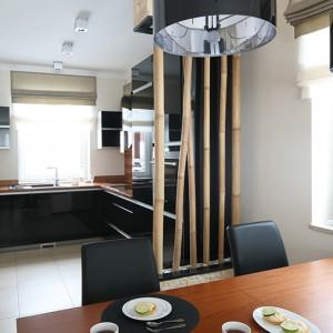 Kuchnię i jadalnię symbolicznie wydziela bambusowa dekoracja umieszczona we wbudowanych donicach. Nowoczesna kuchnia nie zabrała sporo przestrzeni, została też ergonomicznie zorganizowana, dzięki czemu gotowanie w niej to przyjemność. Fot. Bartosz Jarosz.