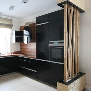 Sprzęty AGD, wpuszczone w zabudowę, również oszczędzają miejsce. Wybrano modele z czarnego szkła, w srebrnym wykończeniu, które komponują się z czernią mebli. Na blatach roboczych i ścianach pojawia się drewno. Fot. Bartosz Jarosz.