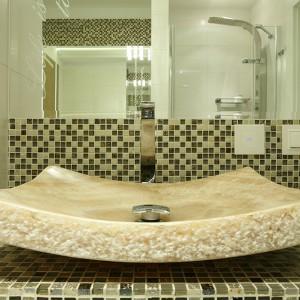 Kamienne umywalki, sprowadzone z Bali, maja formę misy. Na lustrze nad nimi wypiaskowano cytat, który multiplikuje zwierciadło nad wanną. Fot. Bartosz Jarosz.