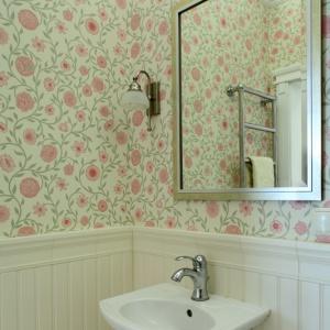 Toaleta na dole jest lekka i zwiewna. Cukierkową tapetę na ścianach połączono z frezowanym MDF-em oraz listwami z poliuretanu. Fot. Monika Filipiuk-Obałek.