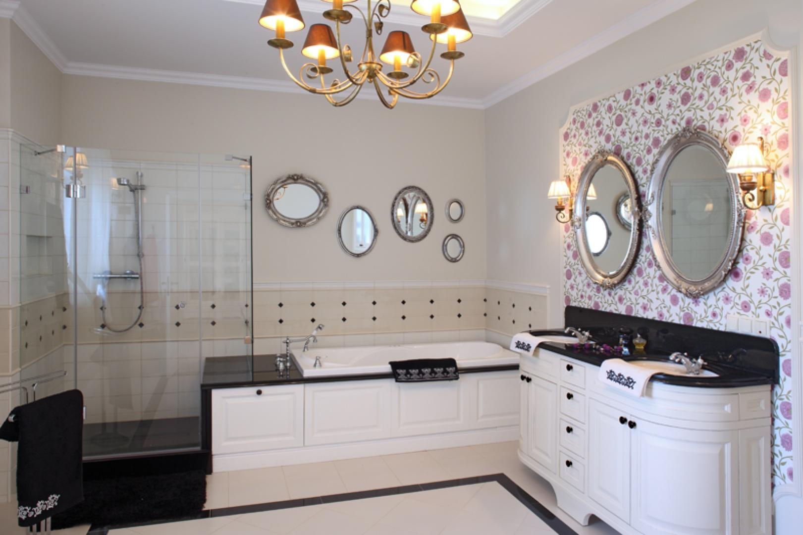 W aranżacji łazienki dominuje drewno (białe fronty meblowe i obudowa wanny) oraz granit. Efektowne tło stanowi beżowa okładzina ceramiczna z dekoracyjnymi czarnymi insertami Ceramiche Grazia oraz tapeta z motywem kwiatowym. Fot. Monika Filipiuk-Obałek.