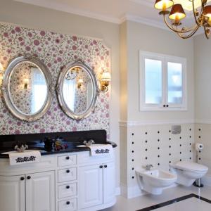 Motyw kwiatowy, tak bardzo charakterystyczny dla stylu angielskiego, widać także w łazience. Tapeta ociepla wnętrze, doskonale korespondując z czarnym granitem i białymi drewnianymi szafkami. Fot. Monika Filipiuk-Obałek.