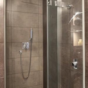 """Kabina prysznicowa została umieszczona we wnęce i  przesłonięta drzwiami z serii """"Niven"""" marki Koło; zamiast brodzika w posadzce umieszczono odpływ liniowy marki Kessel z pokrywą wykończoną płytkami. Fot. Bartosz Jarosz."""