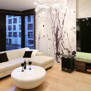 Jedna ze ścian w salonie wyróżnia się szczególnie. Zdobi ją wyrazista fototapeta, będąca perełką pośród spokojnej, stonowanej kolorystyki. Fot. Bartosz Jarosz.