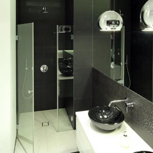 Szklane drzwi prysznicowe z subtelnymi profilami wykonano na zamówienie. Zrezygnowano tu z tradycyjnego brodzika. Zastąpił go odpływ liniowy firmy Kessel zamontowany w podłodze. Fot. Bartosz Jarosz.