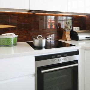 Wyposażenie strefy gotowania oraz pieczenia stanowią piekarnik, płyta grzejna (Siemens) oraz  okap meblowy. Ukryty pod szafką podkreśla jednolity charakter zabudowy meblowej. Fot. Bartosz Jarosz.