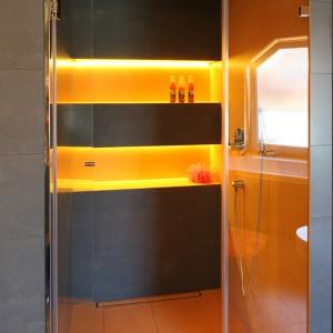 Prysznic jest przestronny i komfortowy. Podczas kąpieli można korzystać z deszczownicy oraz rączki natrysku. Zamiast brodzika, odpływ liniowy w posadzce z pokrywą wypełnioną płytkami. Podświetlone wnęki ścienne wyglądają efektowne; są także praktyczne. Fot. Bartosz Jarosz.