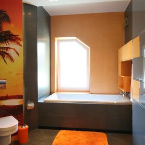 """Okno w łazience to dodatkowa porcja światła. Ścianę wokół niego wykończono płytkami w kolorze pomarańczowym (""""View Orange""""), pozostałe powierzchnie – szarym (""""View Grey"""") z oferty Atlas Concorde. Fot. Bartosz Jarosz."""