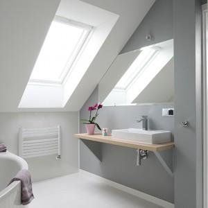 Ogólnodostępna łazienka skąpana jest w bieli i delikatnych szarościach, które przełamują jedynie elementy z jasnego drewna i dodatki w kolorze fioletu. Fot. Bartosz Jarosz.