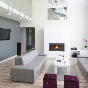 Salon z ogromnymi, prawie pięciometrowymi oknami, otwierający się na dwie kondygnacje jest nowoczesny, minimalistyczny, ale w żadnym razie nie zimny. Fot. Bartosz Jarosz.