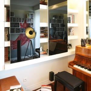 Fronty tej szafy, wykonane z czarnego szkła lacobel (klejonego do płyty MDF), zamontowane są częściowo do sufitu i częściowo do dolnej półki z płyty gipsowo-kartonowej. Pięknie odbijają światło. Fot. Bartosz Jarosz.