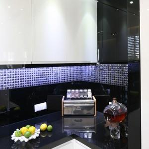 """Ścianę nad blatem zabezpieczają tafle czarnego szkła Lacobel połączone z efektowną mozaiką """"Fat Cube"""" Dunin, również w kolorze czarnym, która podświetlona przybiera barwę błękitu (to efekt kumulacji światła w grubym szkle). Fot. Bartosz Jarosz."""