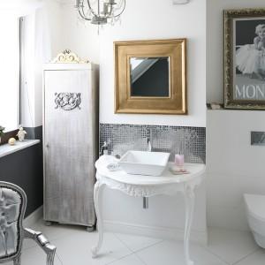Plakat Marilyn oprawiony w grubą, zdobioną ramę nadaje łazience oryginalnego charakteru. Wpisuje się także w aranżację wnętrza spowitą  srebrem, bielą i odrobiną złota. Projekt: Magdalena Konochowicz. Fot. Bartosz Jarosz