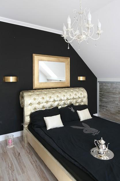 Na czarnej ścianie wyśmienicie prezentuje się lustro w masywnej, złotej ramie oraz kinkiety. Wyeksponowane jest także pikowane wezgłowie łóżka, które właścicielka sama zaprojektowała. Fot. Bartosz Jarosz.