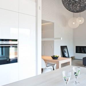 """Lekka i elegancka forma zabudowy idealnie współgra z nowoczesnym stylem mieszkania, otwarta na salon kuchnia stanowi jego integralną część. Dopełnieniem projektu są wiszące lampy """"Random Light"""" Moooi, nad wyspą kuchenną – czarne, w salonie - białe. Fot. Rafał Owczarski."""